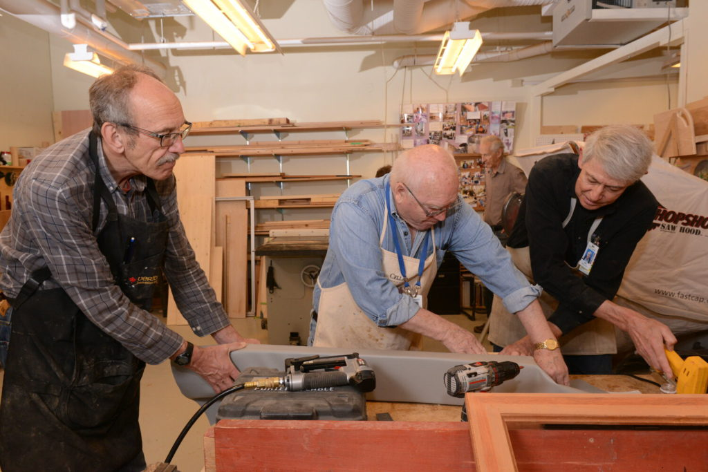 Three Tetra volunteers working with a saw in a wood working shop.