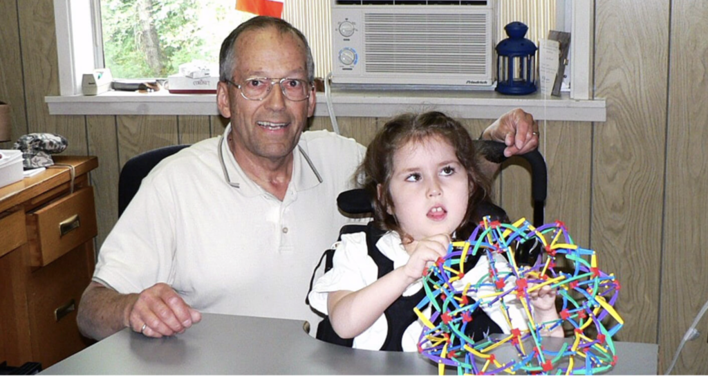 Tetra volunteer posing with young child with sensory toy.